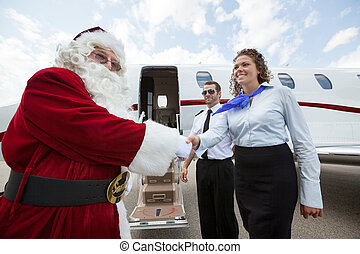 Airhostess And Pilot Welcoming Santa Against Private Jet -...