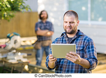 Mid adult carpenter using digital tablet with coworker...