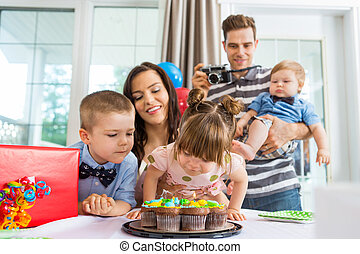 Family Watching Girl Blowing Out Candles On Birthday Cake -...