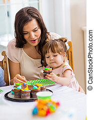 Mother With Girl Eating Cupcake At Birthday Party
