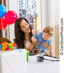Mother Holding Boy With Messy Hands Covered With Cake Icing