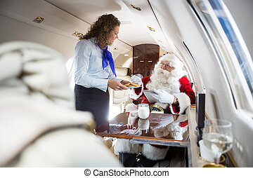 Airhostess Serving Cookies To Santa In Private Jet - Mid...