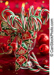 Christmas decoration - Candy canes in a glass on red...