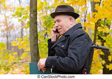 Senior man in a wheelchair chatting on his mobile phone with...
