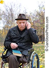 Elderly disabled man in a wheelchair in a park - Elderly...