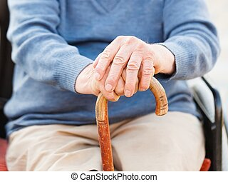 Old hands on stick - Closeup of an old man's hand holding...