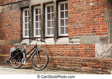 Retro bike against the brick wall of an old building with...