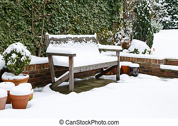 Garden patio bench with snow - Snow covered garden bench on...