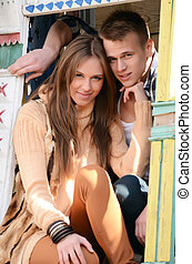 Young enamoured pair in a window old wooden the house
