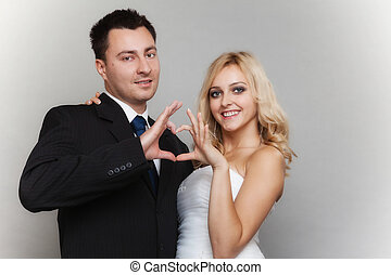 Portrait of happy bride and groom showing heart sign -...