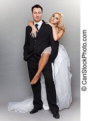 Happy married couple bride groom on gray background -...