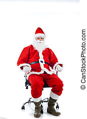 Young Santa Claus sitting on an office chair - Young Santa...