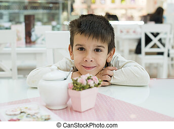Child on table in confectionery Close up pink table