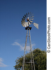 Windmill and Blue Skies - A towering vintage windmill with a...