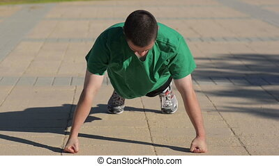 Doing push-ups on knuckles - Boy doing push-ups on his...