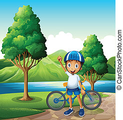 A smiling young boy at the riverbank with his bike -...