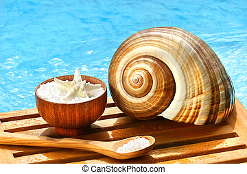 Bath salts and sea shell by the pool