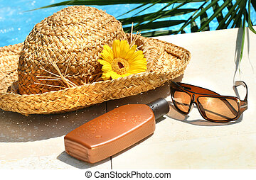 Straw hat, glasses and suntan lotion by the pool