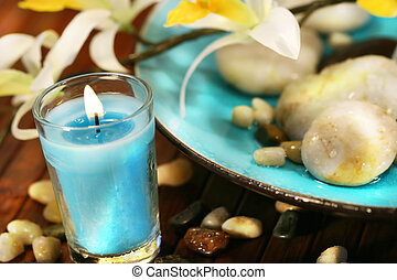 Blue aromatherapy candle and spa stones