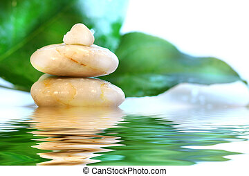 Spa stones with leaves with water reflection