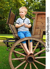 Boyhood Memories - Old-fashioned little boy sitting at a...