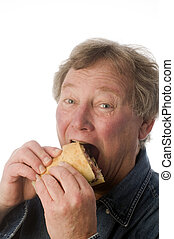 man eating large sandwich - senior middle age man eating...