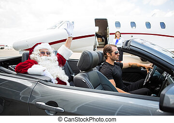 Portrait of Santa waving hand from convertible with private...