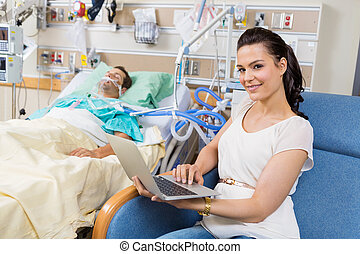 Woman With Laptop Sitting By Male Patient In Hospital -...