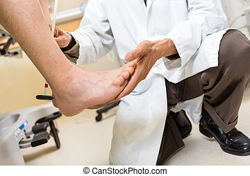Doctor Examining Patients Foot In Hospital - Low section of...