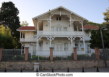 Old white wooden house in a garden