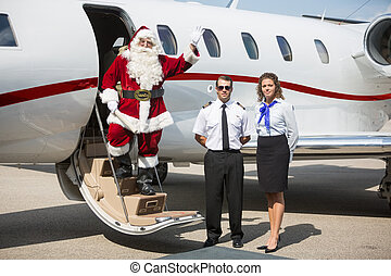 Santa Waving Hand On Private Jet - Portrait of Santa waving...