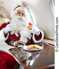 Santa Eating Cookies While Holding Milk Glass In Private Jet...