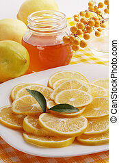 honey and lemon on a plate - Flavored honey and lemon on a...