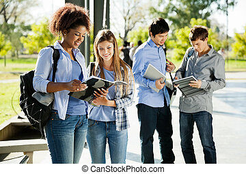 Students Reading Books In University Campus - Happy young...
