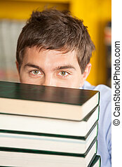 Student Peeking Over Piled Books In University Library