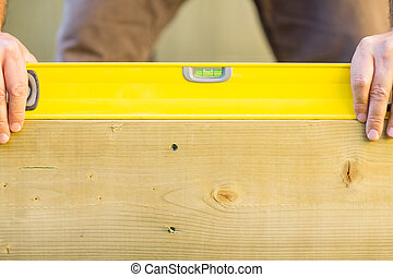 Worker Holding Spirit Level On Wood Outdoors - Closeup of...