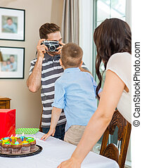 Father Taking Picture Of Birthday Boy And Woman