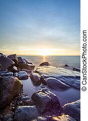 SunriseLake Superior - Rocky shore of Lake Superior during...