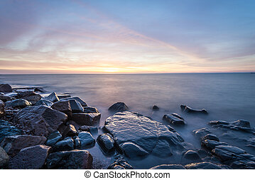 SunriseLake Superior - Rocky shore of Lake Superior during...