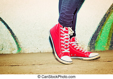 Close up of red sneakers worn by a teenager. Grunge graffiti...