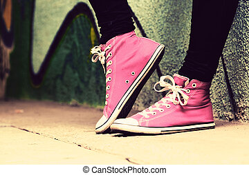 Close up of pink sneakers worn by a teenager. Grunge...