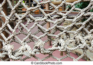 Rope - Brown rope stacked atop nets is patterned.