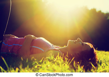 Young pretty woman lying on the grass at summer sunset....
