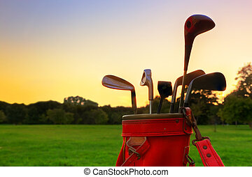 Golf equipment. Professional golf clubs at sunset - Golf...