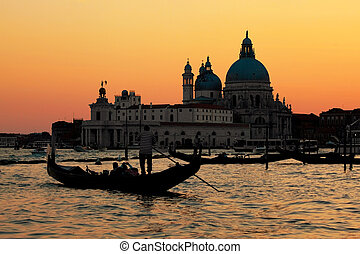 Venice, Italy. Gondola on Grand Canal at sunset. Basilica...