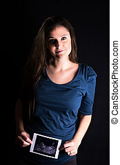 Pregnant woman with scan - Low key studio portrait of a...