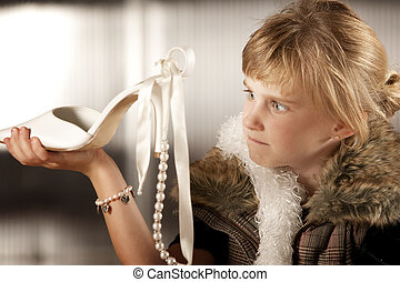 Cute young girl looking scornfully at an adult shoe