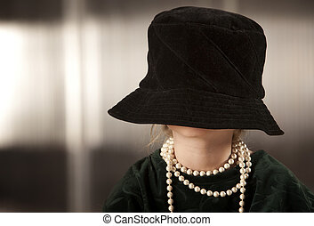 Girl with her face in her hat - Funny young girl with her...