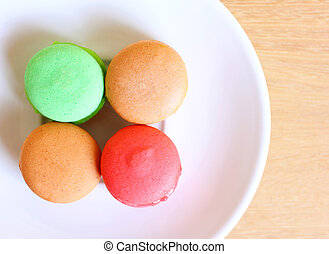 Tasty colorful macaroons on wooden background