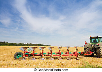 Agriculture tractor ready to plow stubble field -...